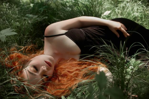 Romantische frau mit dem roten haar, das im gras liegt Premium Fotos