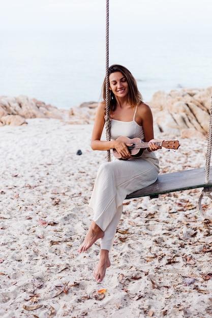 Romantische junge glückliche ruhige kaukasische frau mit ukulele am tropischen felsigen strand bei sonnenuntergang Kostenlose Fotos