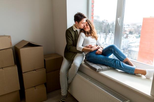 Romantische junge paare, die auf fensterbrett in ihrer neuen wohnung sitzen Kostenlose Fotos