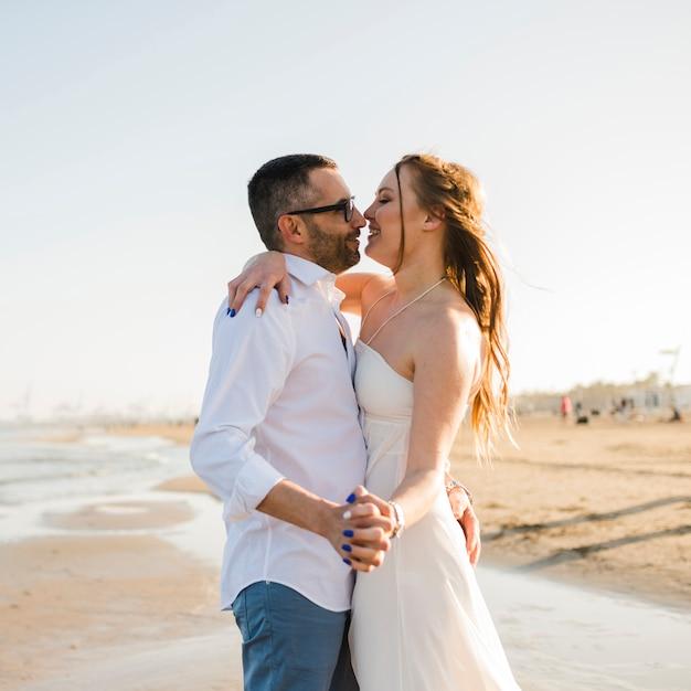 Romantische junge paare, die hand des anderen genießend am strand halten Kostenlose Fotos
