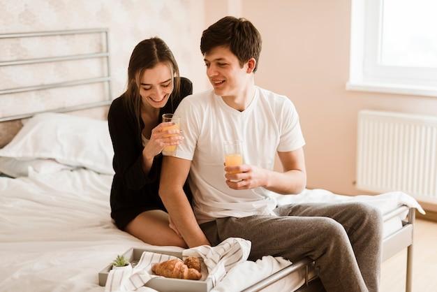 Romantische junge paare, die im bett frühstücken Kostenlose Fotos