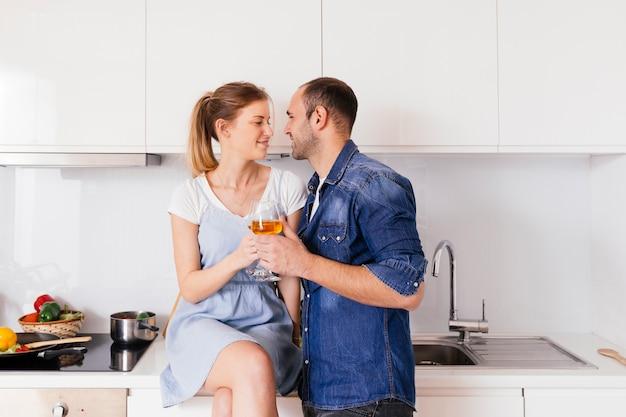 Romantische junge paare, die in der hand weingläser einander betrachten halten Kostenlose Fotos