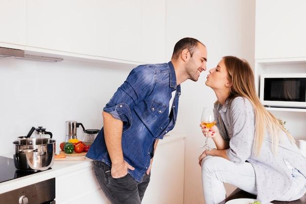 Romantische junge paare, die in der küche küssen Kostenlose Fotos