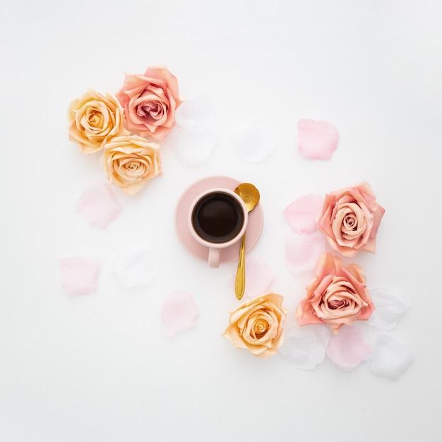 Romantische komposition mit einer rosa tasse kaffee und rosen Kostenlose Fotos