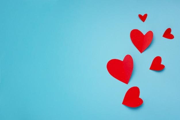 Romantische komposition mit roten herzen auf blauem hintergrund mit copyspace für text Kostenlose Fotos
