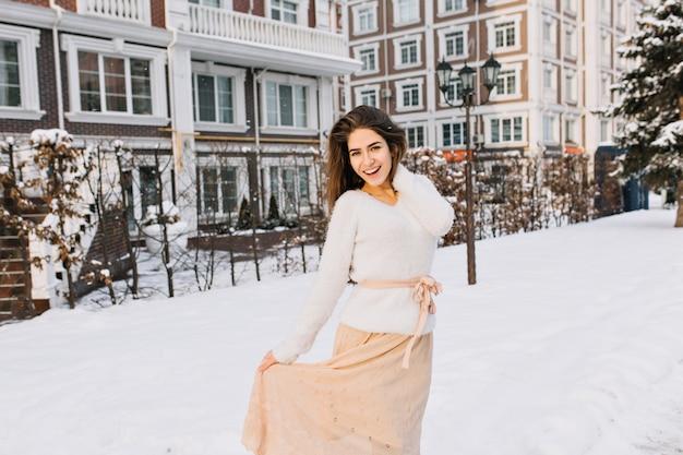 Romantische langhaarige frau im rock posiert auf der straße voller schnee mit laterne. außenporträt der lächelnden schüchternen frau im weißen pullover, der spaß im kalten wintertag hat. Kostenlose Fotos