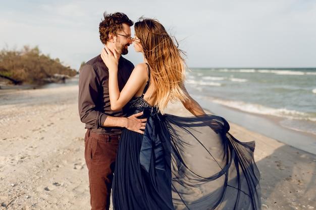 Romantische momente des schönen paares, der modischen frau und des modischen mannes, die draußen in der nähe des meeres posieren. erstaunliches blaues kleid und lässiges outfit. flitterwochenurlaub. Kostenlose Fotos