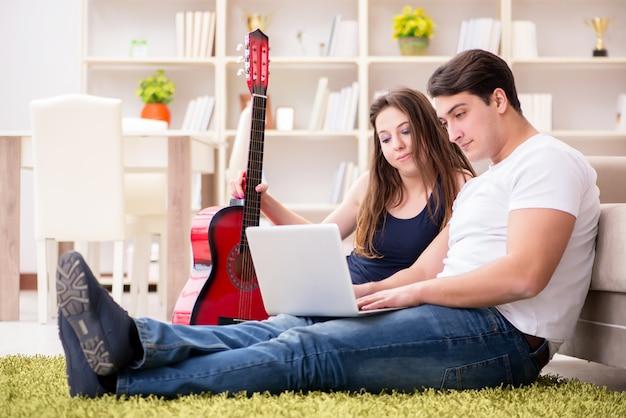 Romantische paare, die gitarre auf boden spielen Premium Fotos