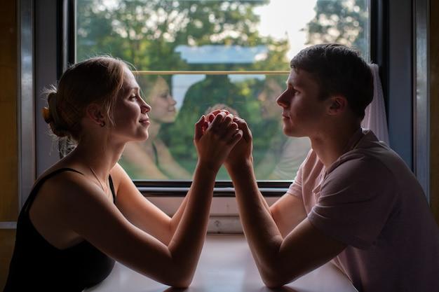 Romantische paare, die hände im zug sich halten. Premium Fotos