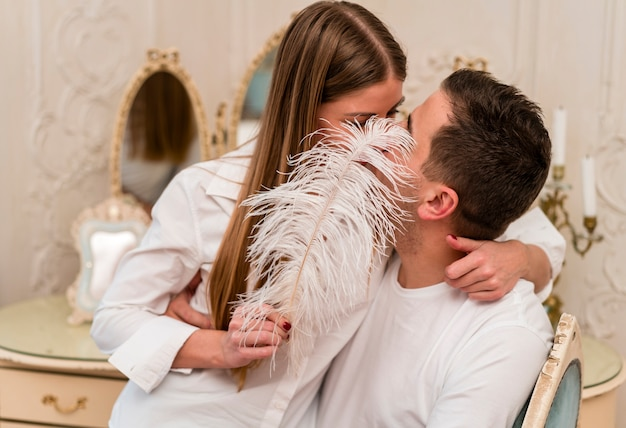 Romantische paare, die münder mit feder küssen und bedecken Kostenlose Fotos