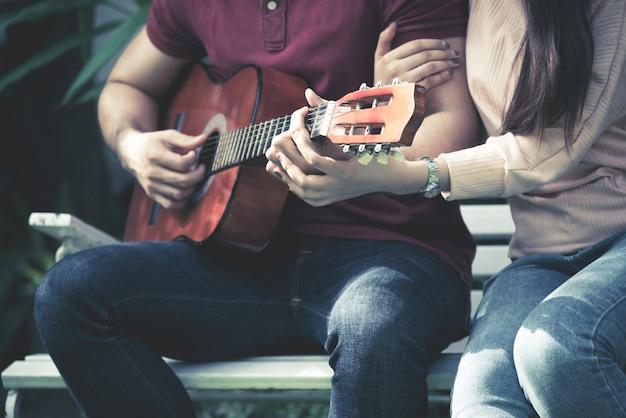 Romantische paare, die zusammen gitarre zum liebes- und valentinstagkonzept spielen. Premium Fotos