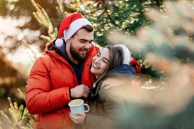 Romantische paare in den weihnachtshüten nähern sich tannenbaum. Premium Fotos