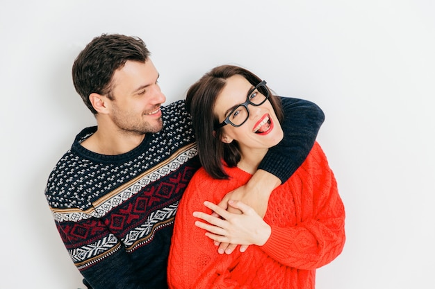 Romantische paare in der liebe umarmen sich und haben spaß zusammen, tragen warme gestrickte strickjacken, stehen gegen weiß Premium Fotos