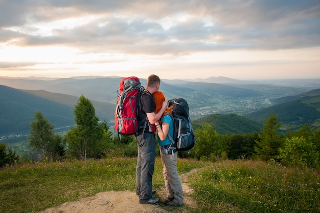 Romantische paarwanderer mit den rucksäcken, die die ansicht von schönem offenem umfassen und genießen, übersehen auf den bergen, den wäldern, den hügeln, dem dorf im tal und dem bewölkten himmel Premium Fotos