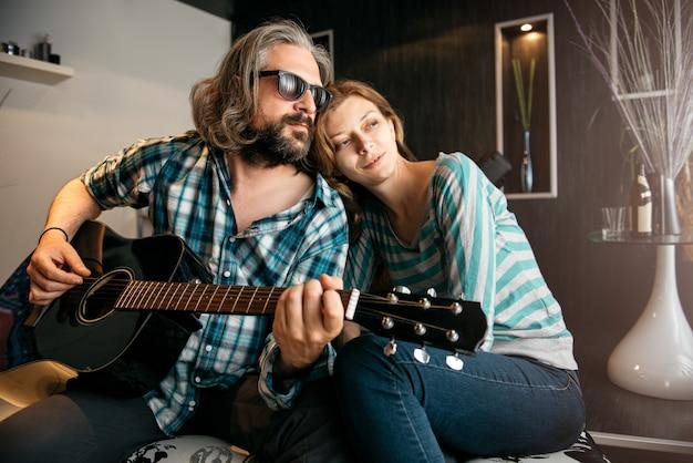 Romantischer mann, der gitarre für seine frau spielt Premium Fotos
