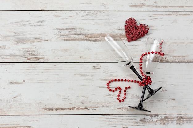 Romantisches abendessen zum valentinstag - rotes herz, gläser mit perlenkette. Premium Fotos