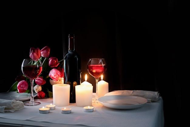 Romantisches candle-light-dinner mit wein, kerzen und tulpenstrauß Premium Fotos