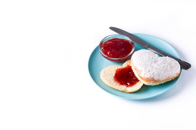 Romantisches frühstück, herzförmiges brötchen und beerenmarmelade auf weißer oberfläche Premium Fotos