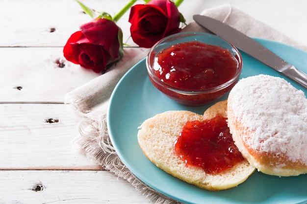 Romantisches frühstück mit herzförmigem brötchen, beerenmarmelade und rosen auf weißem holztisch Premium Fotos