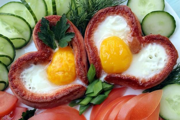 Romantisches frühstück, rührei mit wurst in form von herzen. Premium Fotos