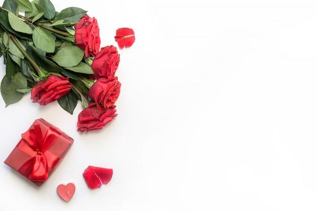 Romantisches gedeck mit blumenstrauß von roten rosen und von geschenk. von oben betrachten. valentinstag. Premium Fotos