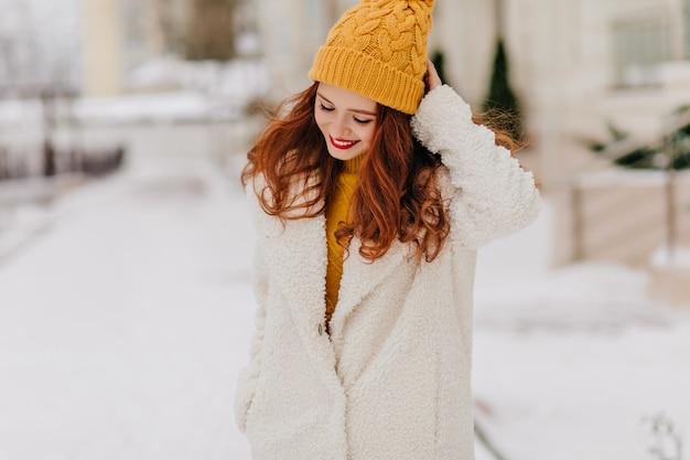 Romantisches ingwermädchen, das während des fotoshootings im freien nach unten schaut. anmutige kaukasische dame, die im winter durch stadt geht. Kostenlose Fotos