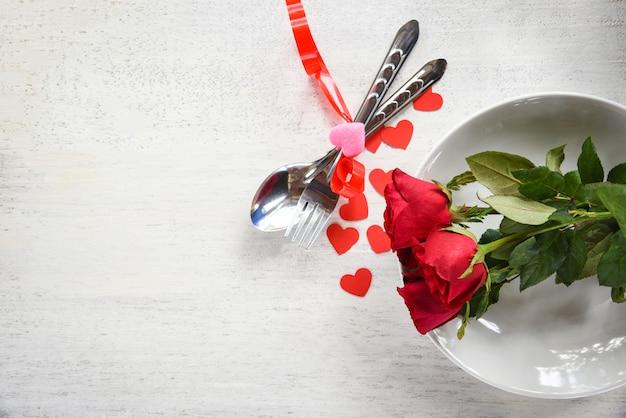 Romantisches liebeskonzept der valentinsgrußabendessen romantische tabelleneinstellung verziert mit gabellöffel rotem herzen und rosen auf platte Premium Fotos