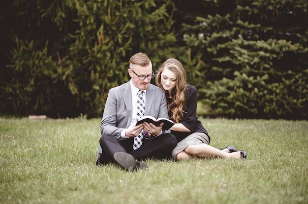 Romantisches paar, das auf rasen sitzt und liebevoll ein buch liest Kostenlose Fotos