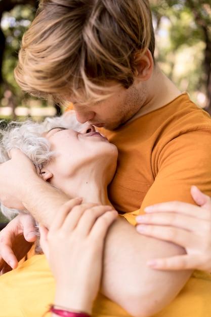 Romantisches paar, das küsst, während draußen im park Kostenlose Fotos