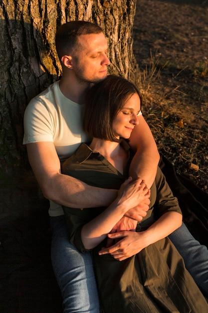 Romantisches paar, das nahe baum sitzt Kostenlose Fotos