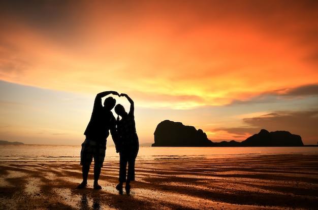 Romantisches paar händchen halten bei sonnenuntergang am