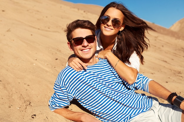 Romantisches paar mit sonnenbrille auf dem sand liegen Kostenlose Fotos