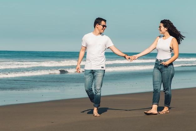 Romantisches paar zu fuß am sonnigen strand Kostenlose Fotos