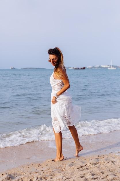 Romantisches porträt der gebräunten frau im weißen sommerkleid am tropischen strand bei sonnenuntergang Kostenlose Fotos