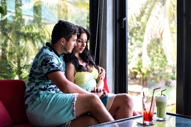 Romantisches porträt des jungen hübschen paares, das im stilvollen café aufwirft, cocktails trinkt und umarmt, perfekte datumsstimmung. Kostenlose Fotos