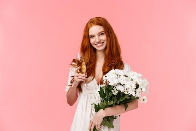 Romantisches rothaariges mädchen mit schönem blumenstrauß im weißen kleid, glaschampagner haltend und lächelnd Premium Fotos