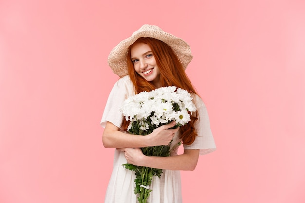 Romantisches rothaariges mädchen mit schönem blumenstrauß im weißen kleid Premium Fotos