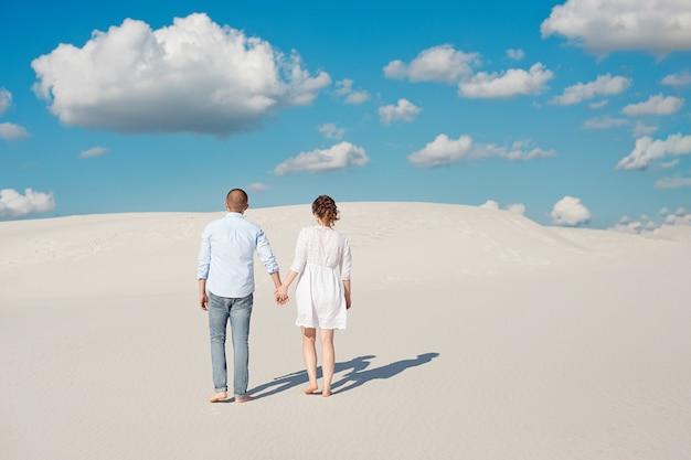 Romantisches verliebtes paar auf dem weißen sand in der wüste. Premium Fotos