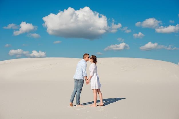 Romantisches verliebtes paar küsst auf dem weißen sand in der wüste Premium Fotos