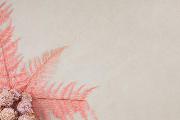 Rosa blätter schmücken einen kleinen haufen popcornbonbons auf marmor. Kostenlose Fotos