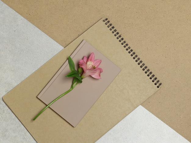 Rosa blume, handwerksalbum auf grauem und braunem hintergrund Premium Fotos