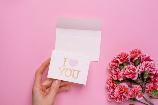 Rosa blumen und hand mit karte ich liebe dich auf rosa Premium Fotos