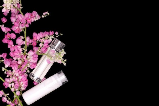 Rosa blumenbergsteiger mit shampoo- und conditionerflaschen Premium Fotos