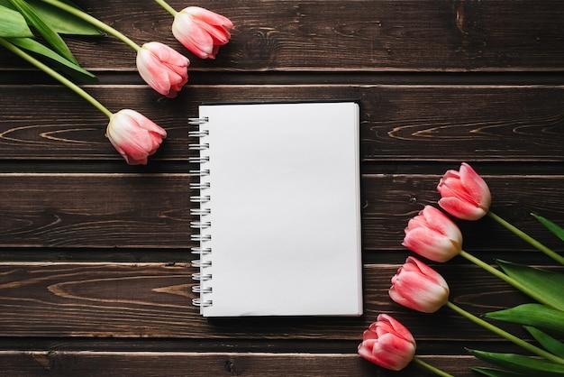 Rosa blumentulpen mit leerem notizblock auf holztisch für grußkarte Premium Fotos