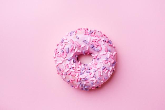 Rosa donut auf rosa. draufsicht flach legen. Premium Fotos
