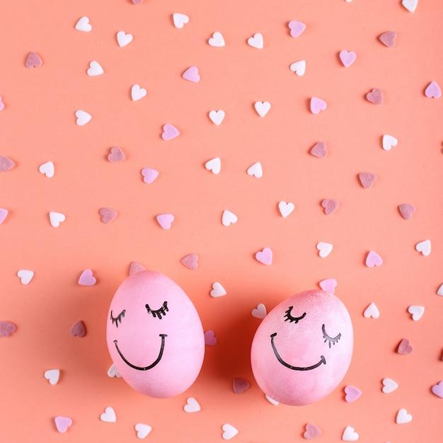 Rosa eier mit gemaltem lächeln auf dem hintergrund mit herzen, glückliche ostern-grußkarte. Premium Fotos
