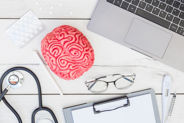Rosa gehirnmodell; pillen; stethoskop; stift; brille; zwischenablage; thermometer; spritze und laptop auf schreibtisch aus holz Kostenlose Fotos