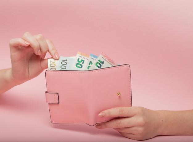 Rosa geldbörse und euro-banknoten in den weiblichen händen auf rosa hintergrund. geschäftskonzept und instagram Premium Fotos