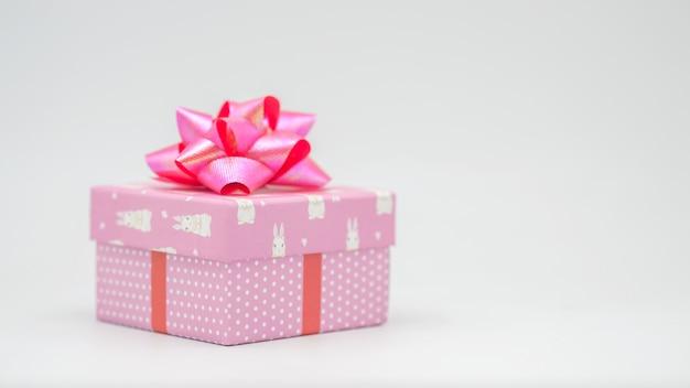 Rosa geschenkbox mit rosa schleife auf weißem hintergrund herzlichen glückwunsch zu verschiedenen anlässen - bilder Premium Fotos