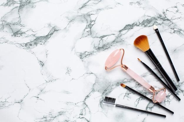 Rosa gua sha massagewerkzeug auf marmor Premium Fotos